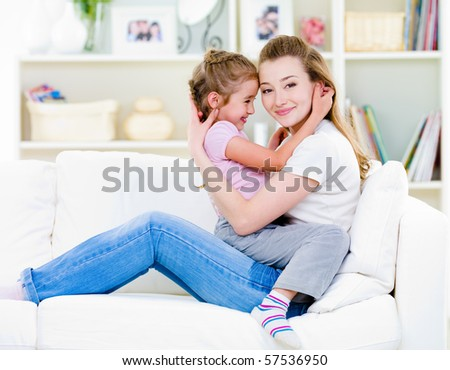Happy mother with little daughter sitting togather on the sofa at home - stock photo