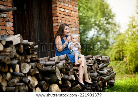 Happy mother with little son spending time in nature by the old house - stock photo