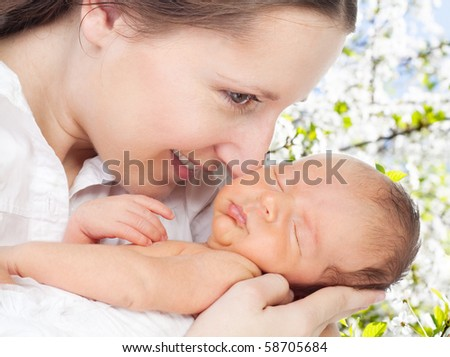 Happy mother with newborn in cherry tree garden