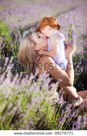 Happy mother with red hair little girl in a lavender field - stock photo