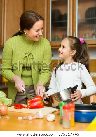 Happy mother with smiling little daughter cooking together at home kitchen - stock photo