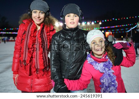 Happy mother with son and daughter on silent disco skating in winter evening - stock photo