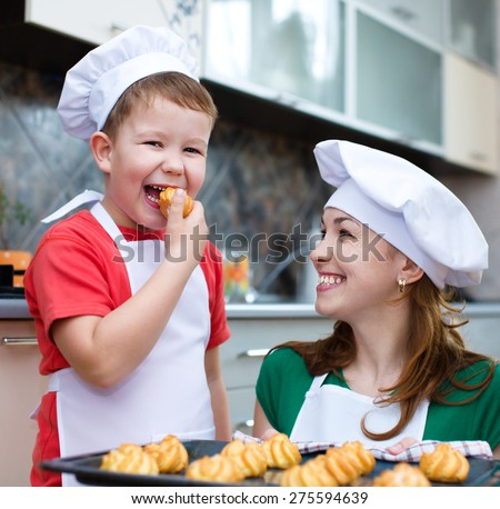 Happy mother with son making bread in the kitchen