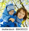 Happy mother with son walking outdoor in autumn - stock photo