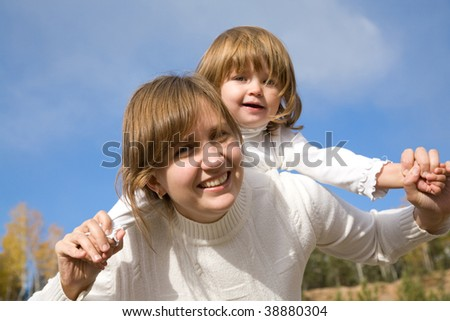 Happy mother with the beautiful little girl against the blue sky - stock photo