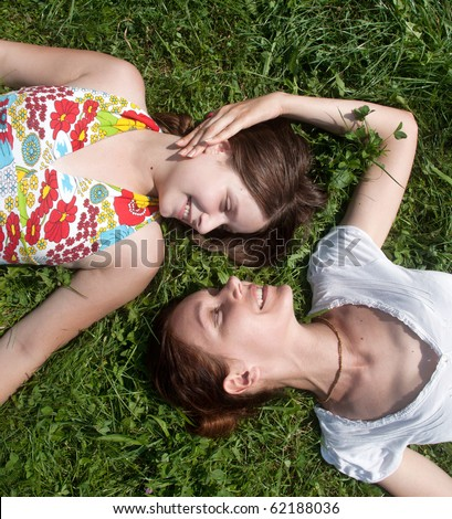 Happy mother with the daughter laying on a grass in park - stock photo