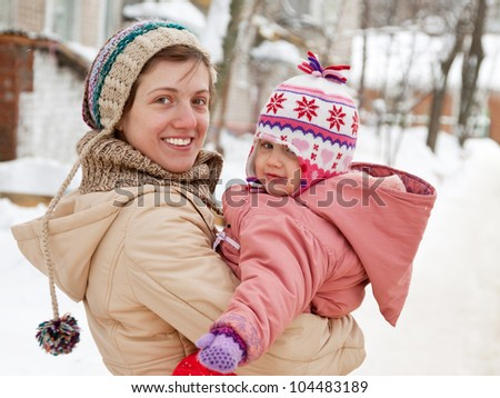 Happy mother with toddler  in winter - stock photo