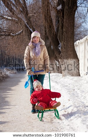 Happy mother with toddler on sled  in winter - stock photo
