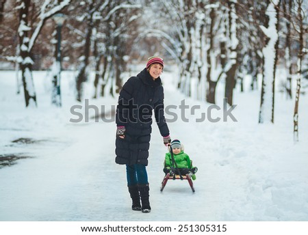Happy mother with toddler on sled in winter park - stock photo