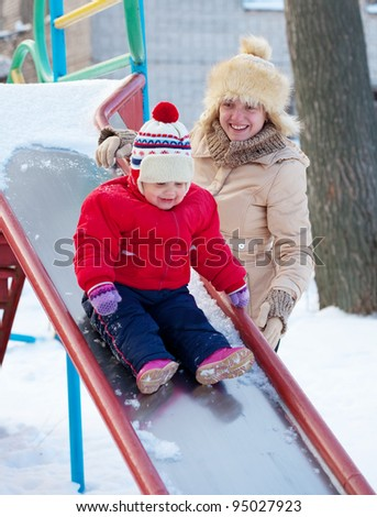 happy mother with  toddler playing on slide in winter - stock photo