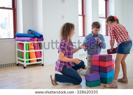 Happy mother with two children play with cubes in light room. - stock photo