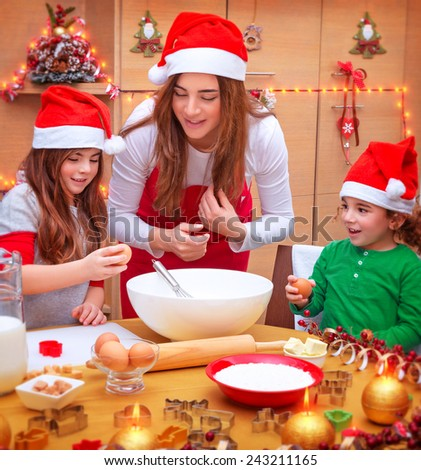 Happy mother with two cute kids wearing red Santa hat cooking festive food on the kitchen, Christmas holidays concept - stock photo