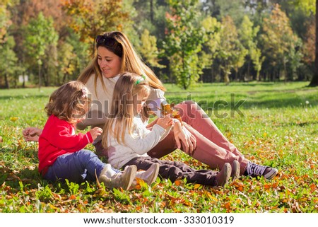 Happy mother with two daughters relaxing in the park.Family lifestyle, autumn season. - stock photo