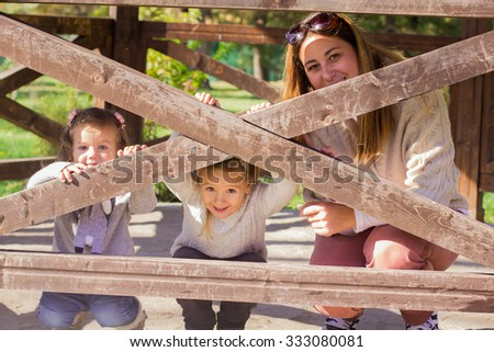 Happy mother with two daughters relaxing in the park.Family lifestyle, autumn season.