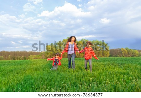 Happy mother with two kids on green field - stock photo