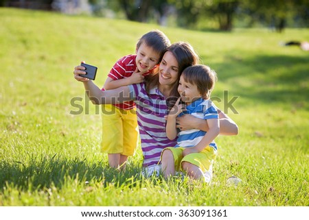 Happy mother with two kids, taking pictures in the park