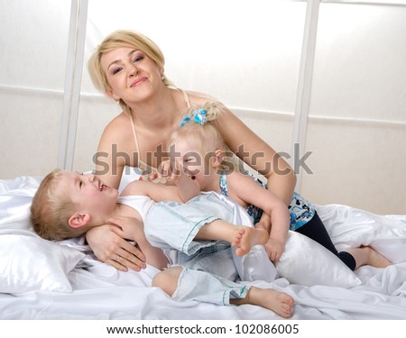 happy mother with young children to bed in the bedroom - stock photo