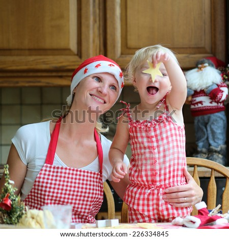 Happy mother, young woman in red apron and santa hat baking christmas cookies together with her little daughter, cute blonde toddler girl, sitting at the table in classic traditional wooden kitchen - stock photo