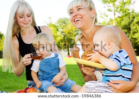 Happy mothers and their babies eating in the outdoors - stock photo