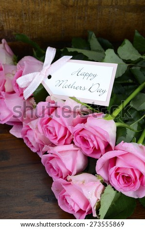 Happy Mothers Day fresh pink roses on dark wood distressed table and background, with gift tag.