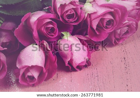 Happy Mothers Day gift of fresh pink roses on a pink distressed wood background, and applied retro vintage style filters. - stock photo