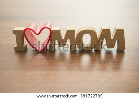 Happy Mothers day. I Love my mom Concept. Red heart and Wooden letters spelling. Image with shadows on table. - stock photo