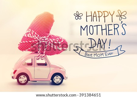 Happy Mothers Day message with a miniature pink car carrying a heart cushion - stock photo