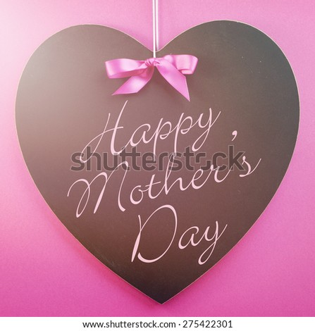 Happy Mothers Day message written on a black blackboard with blue ribbon against a blue background, with applied retro style filters and added lens flare light beam. - stock photo