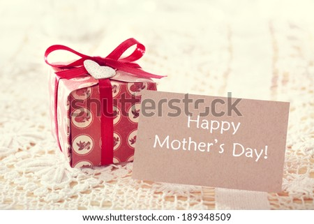 Happy mothers day message written on a card with a hand crafted present box  - stock photo