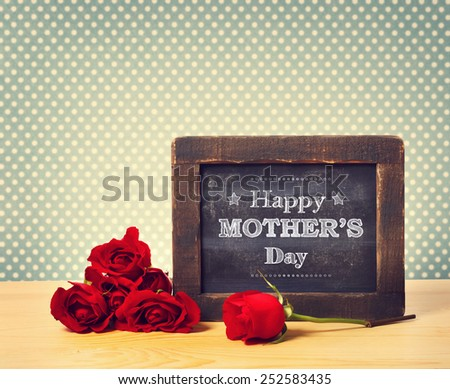 Happy Mothers Day message written on little chalkboard with roses - stock photo