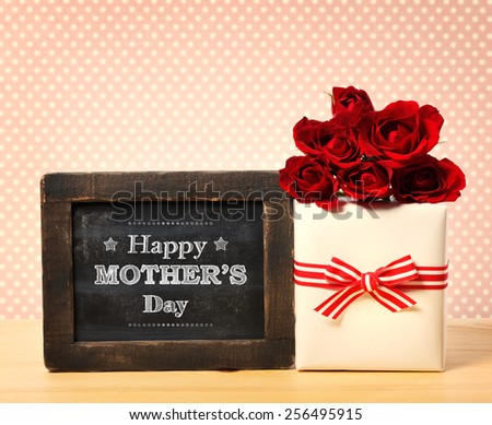 Happy Mothers Day message written on little chalkboard with roses and present box - stock photo