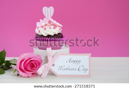 Happy Mothers Day pink and white cupcake on retro style cake stand and pink rose on vintage white wood table, with copy space. - stock photo