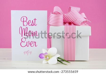 Happy Mothers Day pink and white gift with Best Mom Ever greeting card, on white shabby chic distressed wood table. - stock photo