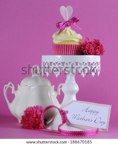 Happy Mothers Day pink heart cupcake on white cupcake stand with greeting gift tag against a feminine pink background. - stock photo