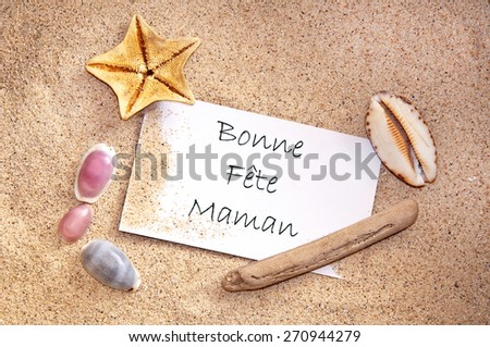 Happy mothers day written in French on a note with sand and seashells - stock photo