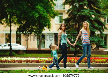 Happy mothers walking together with kid in summer park - stock photo