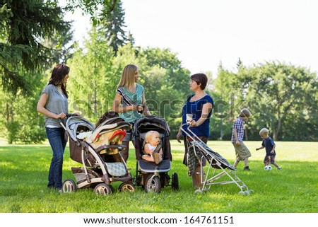 Happy mothers with baby strollers talking in park - stock photo