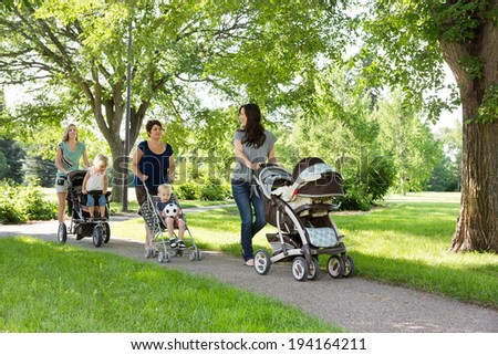 Happy mothers with their baby carriages walking together in park - stock photo