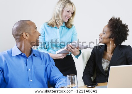 Happy multi ethnic business people communicating with each other - stock photo