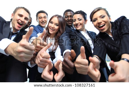 Happy multi-ethnic business team with thumbs up in the office - stock photo