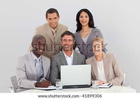 Happy multi-ethnic business team working with a laptop in office together