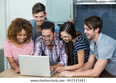 Happy multi-ethnic young friends looking in laptop on table at home