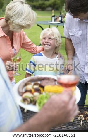Happy multi-generation family enjoying barbecue and wine - stock photo