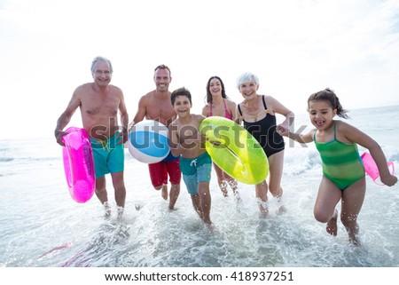Happy multi-generation family enjoying on sea shore at beach - stock photo