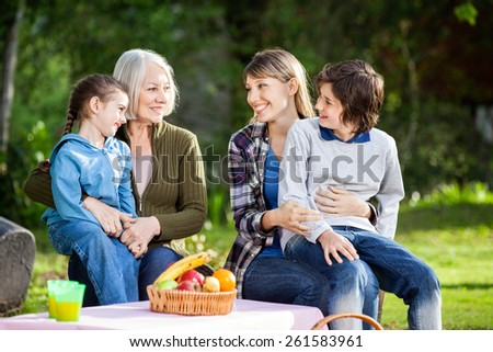 Happy multi generation family enjoying picnic in park - stock photo