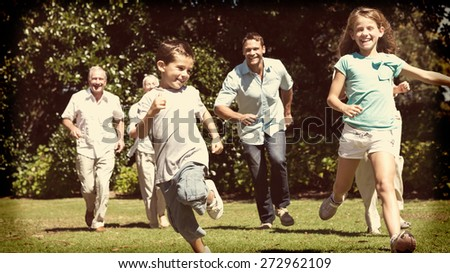 Happy multi generation family racing towards camera in a park - stock photo