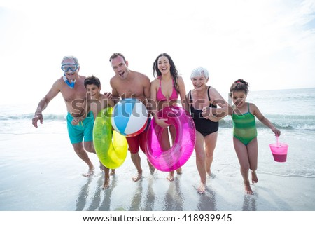 Happy multi-generation family running on sea shore at beach - stock photo