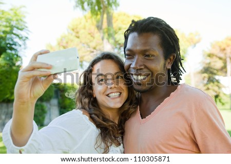 Happy multi racial couple taking a picture with a smartphone.