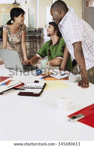 Happy multiethnic business people using laptop at conference table - stock photo