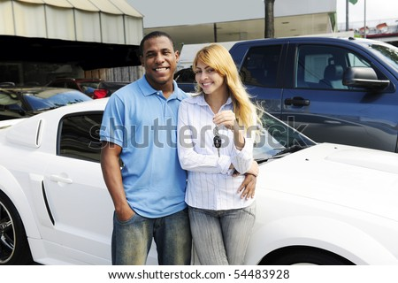 happy multiethnic couple buying a new car - stock photo